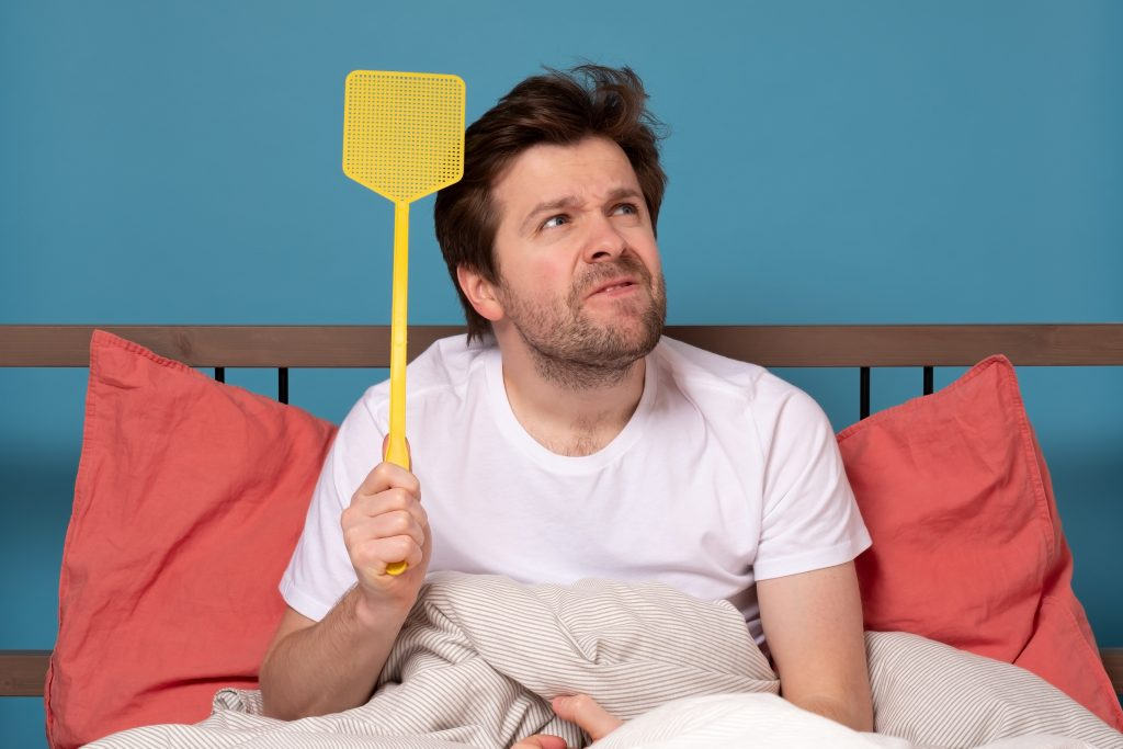 man holding a fly swatter wanting to kill annoying mosquito